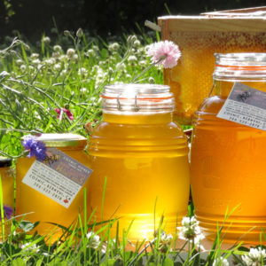 jars of fresh honey in a field of flowers